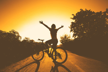 silhouette of woman at sunset with bicycle and happy