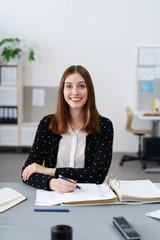 freundliche mitarbeiterin am schreibtisch lächelt in die kamera