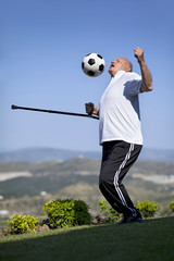 A senior football player with walking stick to head a soccer bal