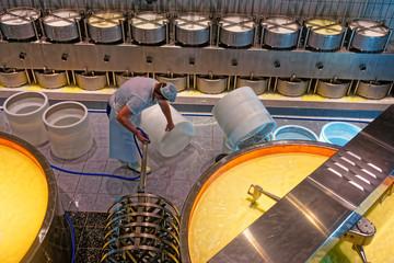 Worker of the cheesemaking factory preparing necessary equipment