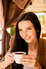 Charming young woman enjoying coffee in cafe