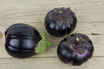 Eggplants on a wooden table with fresh herbs