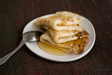 Three pancakes with honey on a white plateau with a spoon. Pancakes with honey on a white plateau