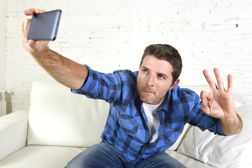 young attractive 30s man taking selfie picture or self video with mobile phone at home sitting on couch smiling happy