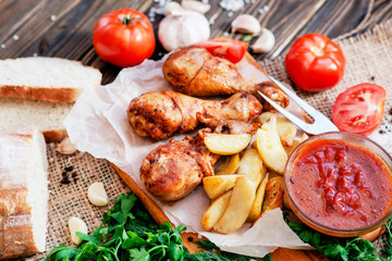 baked chicken legs in garlic marinade with baked potatoes , sauce , tomatoes , bread and herbs on wooden background