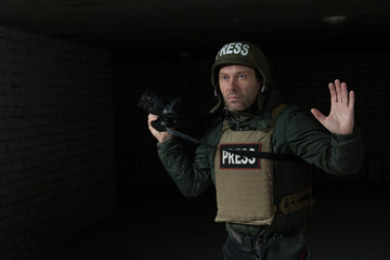 Photojournalist in a helmet and flak jacket wore protective equipment for shooting in hot spot