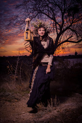 Beautiful young witch with lamp in her hand in sunset