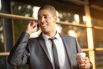 Successful afro businessman talking on mobile and smiling