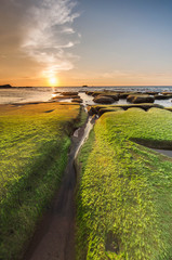 natural channel between two rock with green moss and sunset