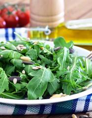 Rucola - Salat mit Salatkernen / Auf Teller, Küchentuch mit Olivenöl und Kirschtomaten