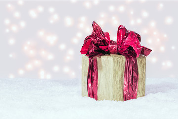 Gift box with a red ribbon on snow against festive lights