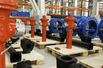 New red fire hydrant on plant`s stock