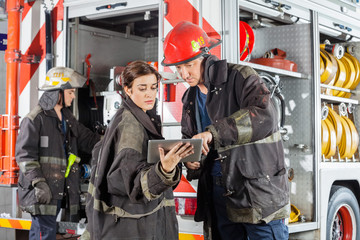 Firefighters Using Tablet Computer Against Truck