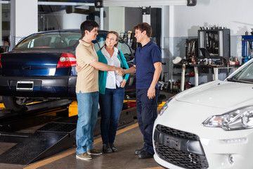 Mechanic Shaking Hand With Couple