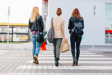 Three girls crossing the street after shopping