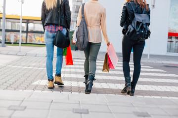 Modern girls rushing across the pedestrian crossing with shoppin