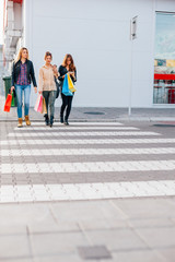 Three girls crossing the street with shopping bags and mobile ph