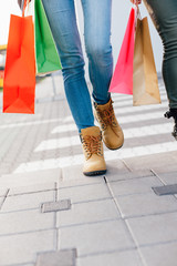 Closeup of girls hold colorful shopping bags and cross the stree