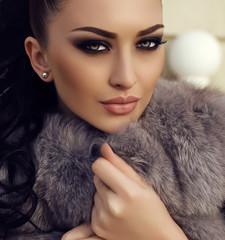gorgeous woman with long dark hair wears luxurious fur coat