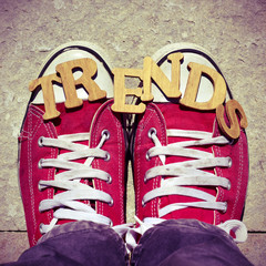 wooden letters forming the word trends and the feet of a young m