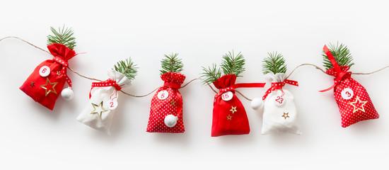 6 Säckchen vom Adventskalender hängende Weihnachtsdekoration zur Weihnachtszeit, traditionell deutsche Weihnachtsgestaltung.