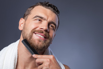 Cheerful young bearded guy with comb and smile