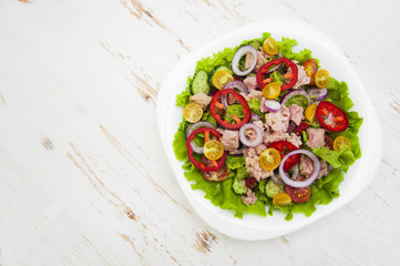 A fresh and colorful tuna salad on a wooden background