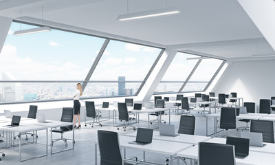 A young woman is looking out the window in the modern bright open space loft office. White tables equipped by modern laptops and black chairs. New York panoramic view.