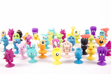 many of colorful funny little toy monsters on a white background