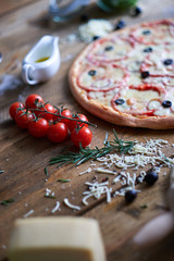 Different ingredients and circle pizza on table.