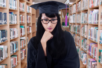Female bachelor with a graduation cloak in library