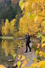 Man photographer, shooting the nature, in fall season