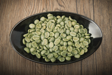 Wall Mural - Black bowl with green coffee beans on the wood