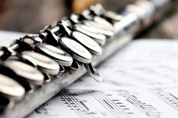 Old silver flute and music notes on rusty table