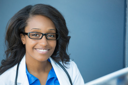 Closeup headshot portrait of friendly, smiling confident female healthcare professional with lab coat, glasses, and stethoscope. Isolated hospital clinic background. Time for an office visit