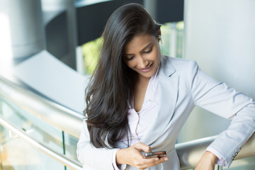 Closeup portrait, young happy business woman in gray white suit dress standing, checking her cellphone, listening to music, isolated on indoors office background. Corporate life success.