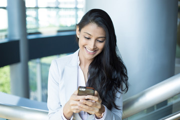 Closeup portrait, young successful happy business woman in light white gray suit, checking her cellphone, isolated on interior indoors office background . Business communication