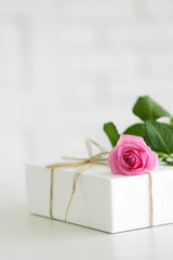 Big white gift box with rose on the table, close up