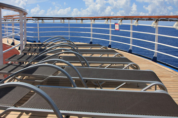 Pool chairs in a row on deck onboard a cruise ship at sea