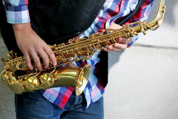 Saxophonist plays jazz outdoors, close up