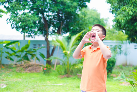Portrait of Asian child yelling, screaming, shouting, hand on hi