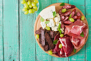 Printed roller blinds Appetizer Antipasto catering platter with bacon, jerky, sausage, blue cheese and grapes on a wooden background