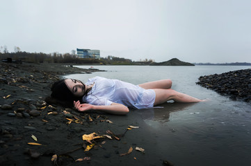 girl lying on dark river