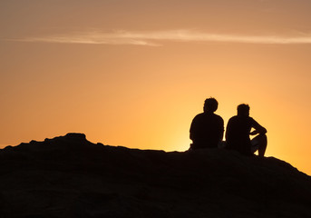 Silhouette of Couple sit arguing on a rock near the sea and watching the sun