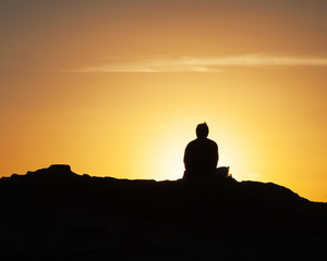 Silhouette of lone man sitting on a rock near the sea and watching the sunset