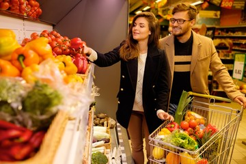 Couple choosing vegetables in a grocery store