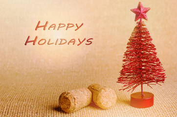 Happy holiday written in red .Red artificial Christmas tree with champagne cork on bright background.