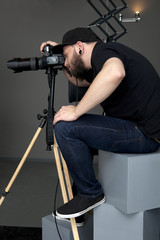 Photographer sits on cubes and photographed in a studio with gra