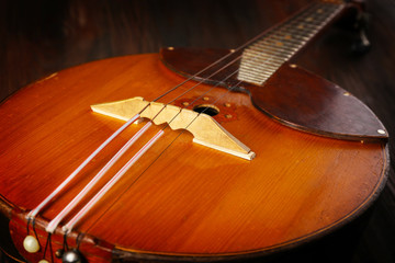 Folk musical instrument domra on wooden surface, closeup