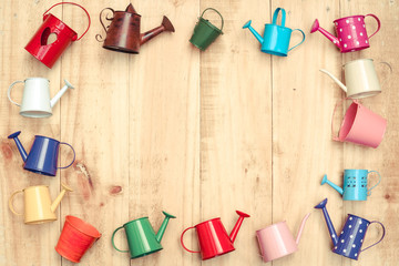 small colorful watering cans and buckets arranged as a picture frame on wood plank background